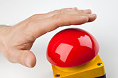 A hand about to press a big red buzzer