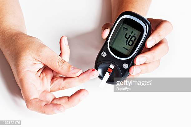 Hand adding drop of blood to diabetic glucometer
