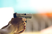 hand aim pistol in academy shooting range with flare and vintage color