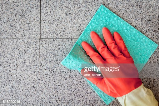 Hand and a blue cloth cleaning on a  wall : Photo