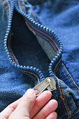 Hand holding Blue Close up Jean zip on denim bag texture blue background. Looking like Female vergina for Contraception Birth control education concept. Canvas textile Fashion industry business design