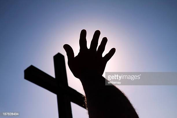 Hand and cross in silhouette