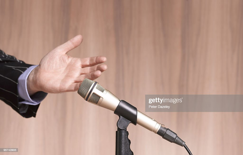 Hand and Microphone against wooden background. : Stock Photo