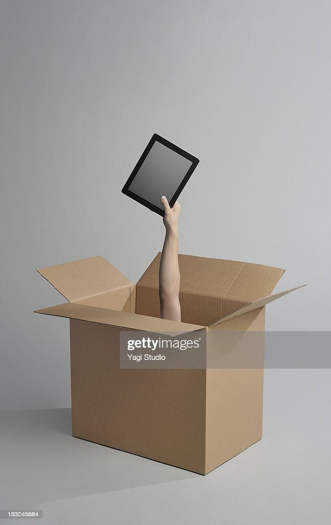 Hand appearing from a cardboard box has digital ta : Stock Photo