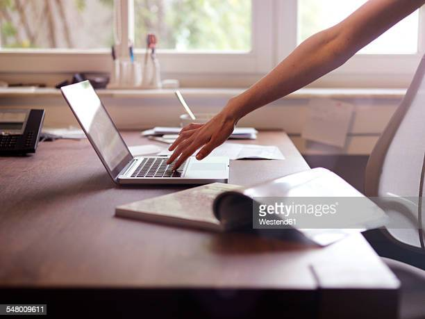 Hand at laptop and magazine on table