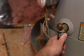 Hand attaches hose to water heater drain to perform maintenance