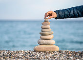Man's hand balancing stack of stones on beach