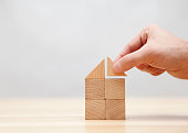 Hand building house with small wooden blocks