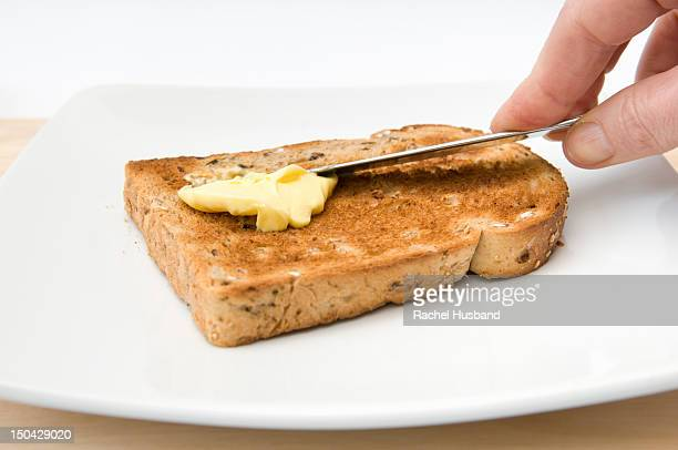 Hand buttering a piece of granary toast