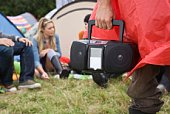 Hand carrying stereo at campsite