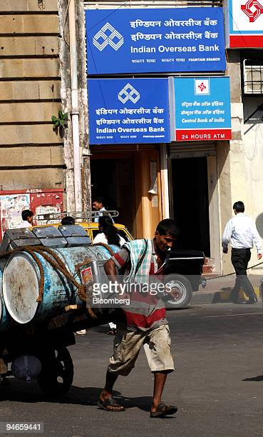 A hand cart puller walks past a branch of Indian Overseas Bank in Mumbai India on Thursday Nov 29 2007 India's economy grew last quarter at the...