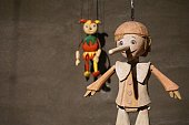 A wooden doll hanging on a wall.