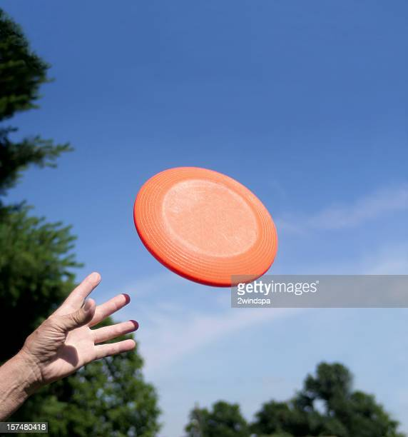 Hand catching orange frisbee against blue sky background