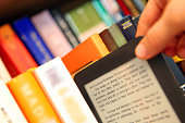 Person taking an e-reader from a book shelf. Selective focus. Very shallow dof. Text in the book is from A Christmas Carol by Charles Dickens (1843).