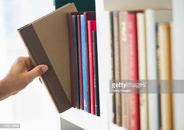 Hand choosing book from shelf