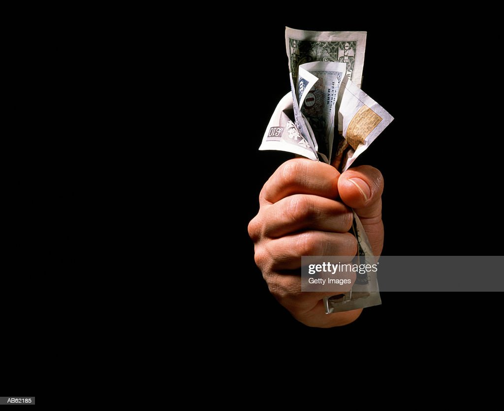 Hand clenching currency, close-up : Stock Photo