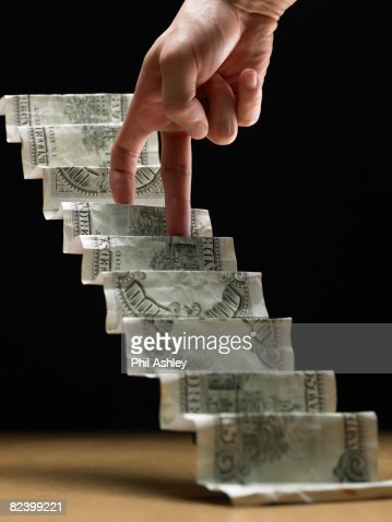 hand climbing up stairs made of dollar bills : Stock Photo