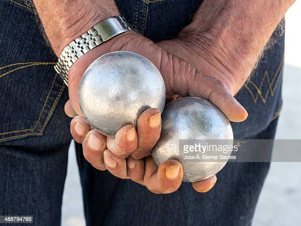 Hand clutching two balls of metal play bocce