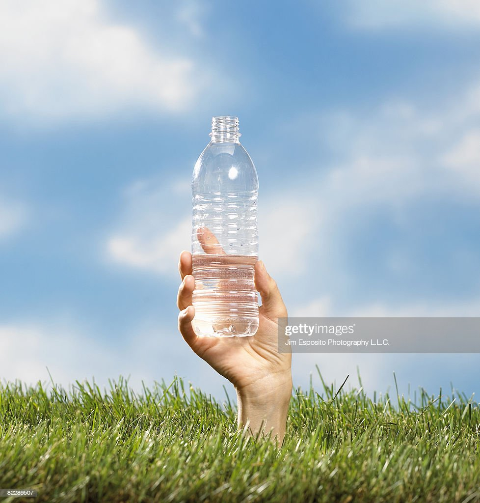 Hand coming out of grass holding water bottle. : Stock Photo