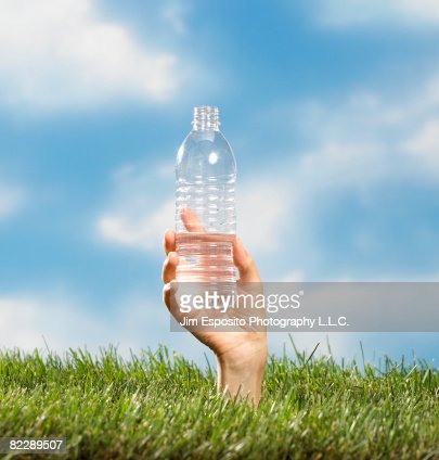 Hand coming out of grass holding water bottle. : Stockfoto