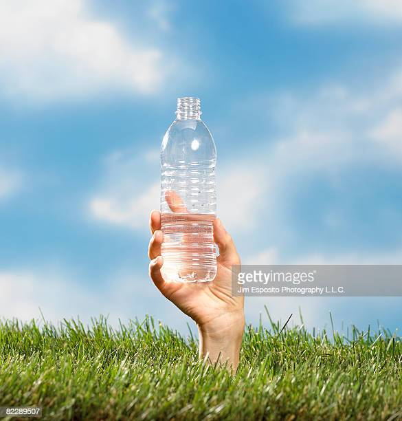 Hand coming out of grass holding water bottle.