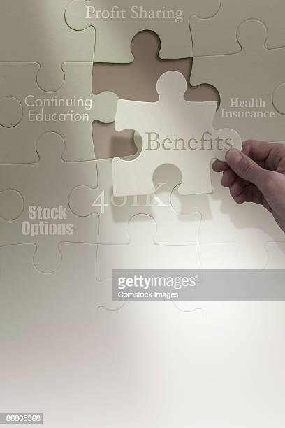 Hand completing employment benefits puzzle