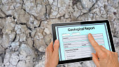 Hand completing online Geological Report on a computer tablet - infront of clay soil background with cracks - technology concept