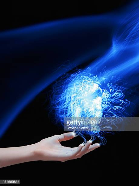 Hand connecting with an ethereal ball of light