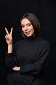 Hand counting - two fingers. Smiling woman in grey turtleneck sweater over dark background showing two fingers, V sign