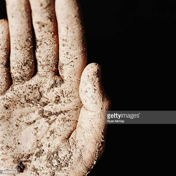 Hand covered in dried mud, close-up