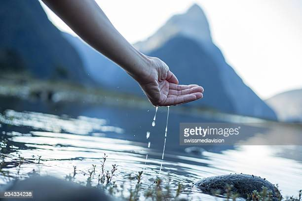 Hand cupped to catch fresh water from the lake-New Zealand