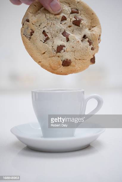 Hand dipping large chocolate chip cookie in small coffee cup