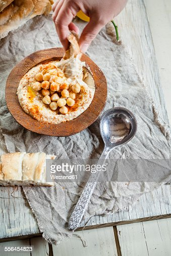 Hand dipping turkish flatbread into hummus