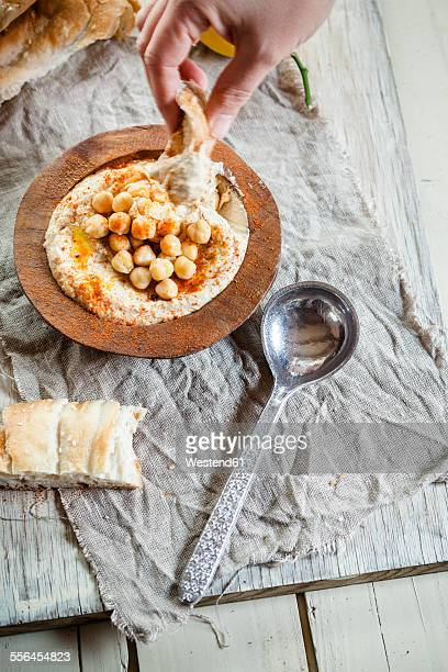 Hand dipping turkish flatbread into hummus