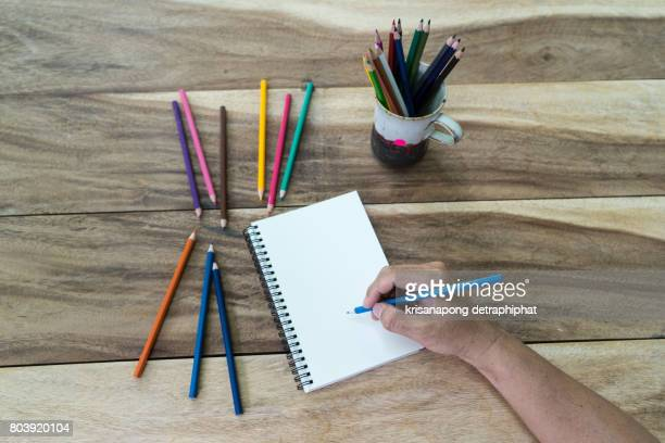 Hand drawing, blank paper and colorful pencils on old wooden table