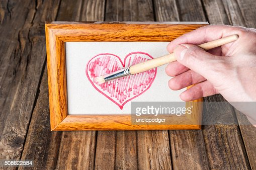 Hand drawing heart in old photo frame : Stock Photo