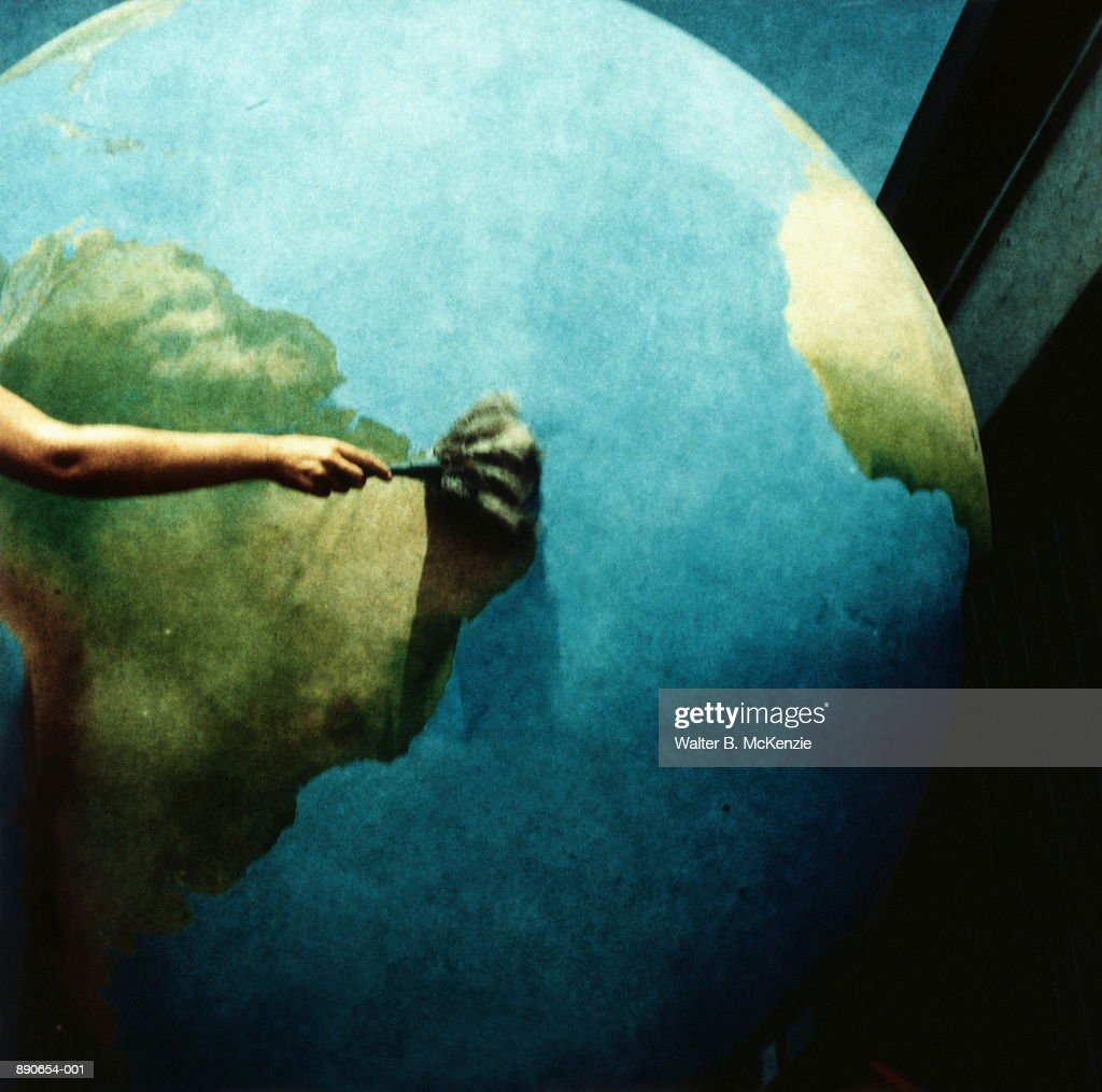 Hand dusting off globe, South America prominent (paper negative) : Stock Photo