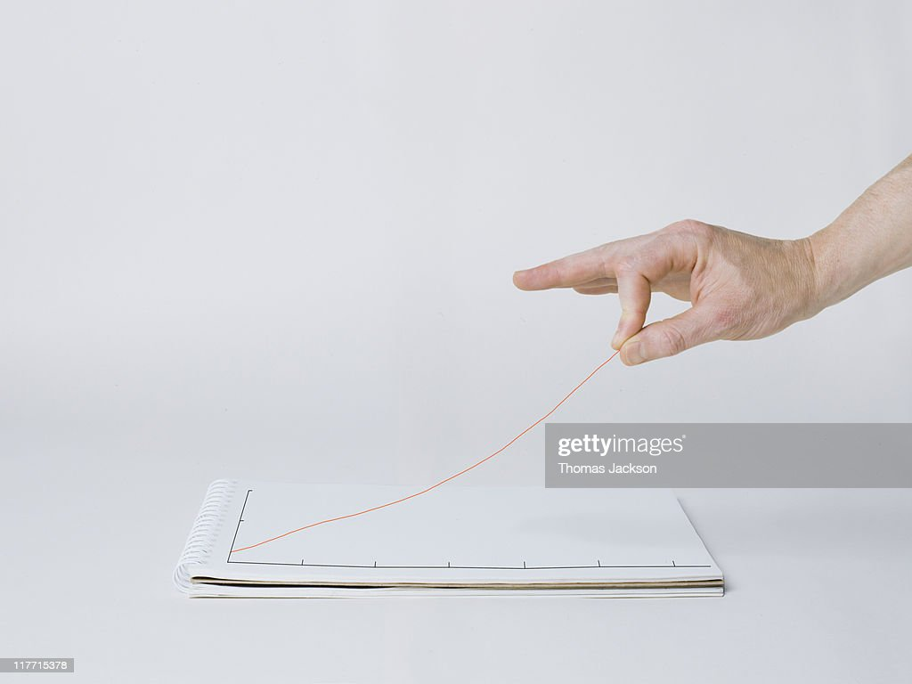 Hand elevating graph line off the page : Stock Photo