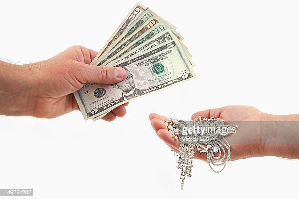 Hand exchanging US banknotes on jewelry