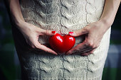 Hand female holding intim heart shepe on a white dress