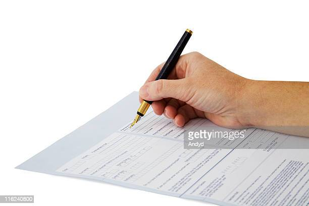 Hand filling a form with a pencil