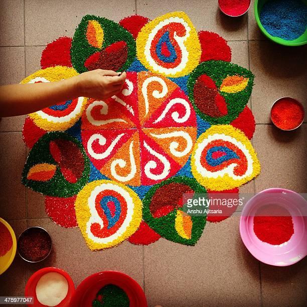 A hand finishing a rangoli