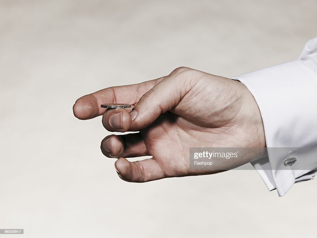 Hand flipping coin : Stock Photo