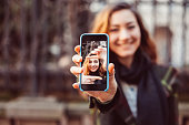 Close up of smiling girl showing hand framing self portrait
