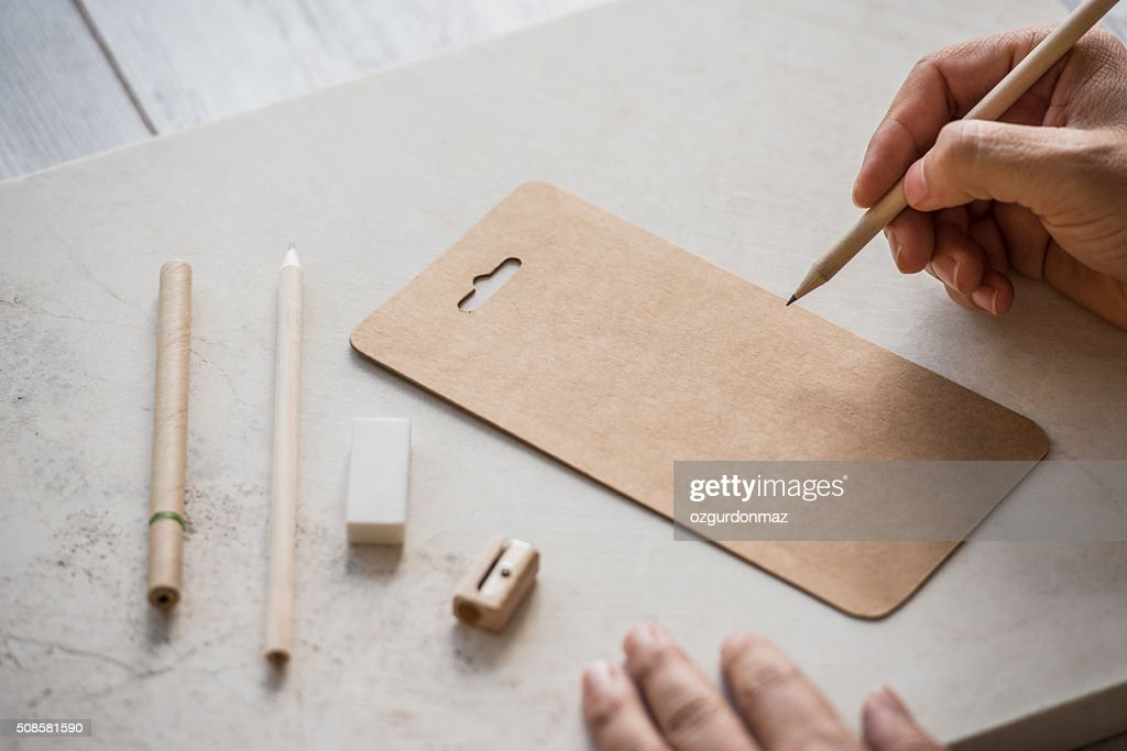 Hand getting ready to write on empty brown paper : Stock Photo