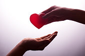 A hand gives a red heart to a hand - blood donation,world blood donor day