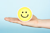 Hand giving hapiness concept. Yellow happy face emoticon.