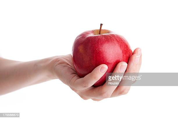 Hand giving red apple