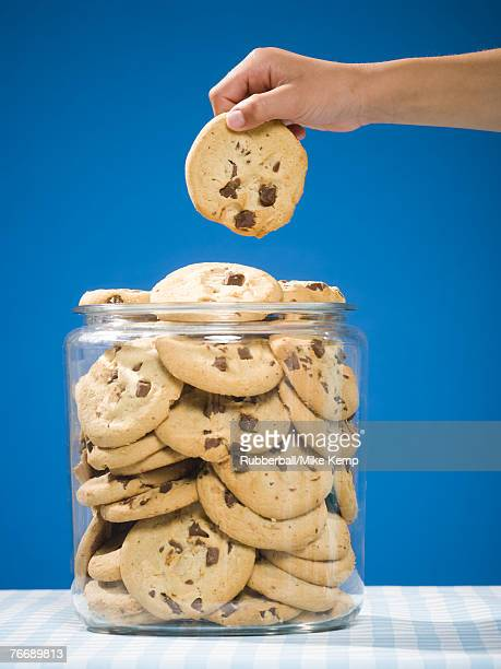 Hand grabbing chocolate chip cookie from jar
