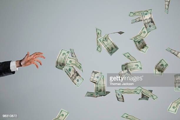 Hand grasping at fluttering money